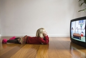 Young girl watching cartoons on television.