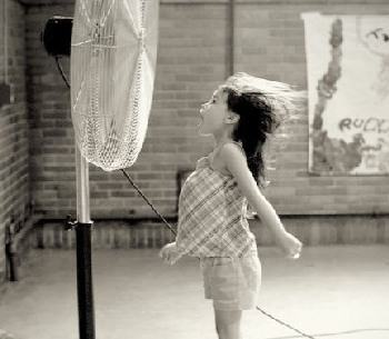 Little girl cooling off in front of a fan.