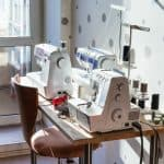 Workshop of seamstress at home - sewing machines and serger on table