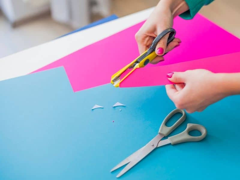 Woman's hand cutting colorful papers